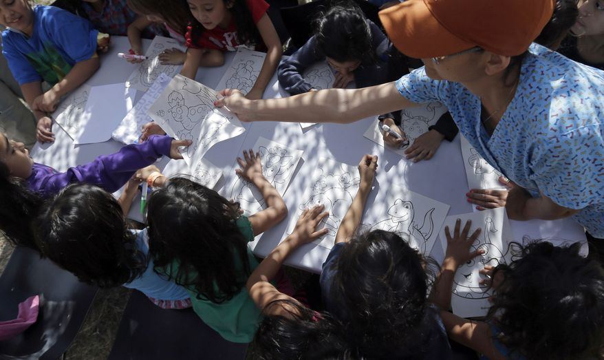 ** FILE ** This June 18, 2014, file photo shows children detainees coloring and drawing at a U.S. Customs and Border Protection (CPB) processing facility in Brownsville,Texas. (AP Photo/Eric Gay, Pool)