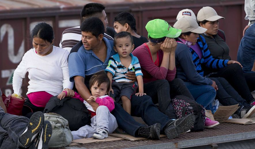 In this July 12, 2014, photo, Central American migrants ride a freight train during their journey toward the U.S.-Mexico border in Ixtepec, Mexico. The number of family units and unaccompanied children arrested by Border Patrol in the Rio Grande Valley has doubled in the first nine months of this fiscal year compared to the same period last year.  (AP Photo/Eduardo Verdugo)