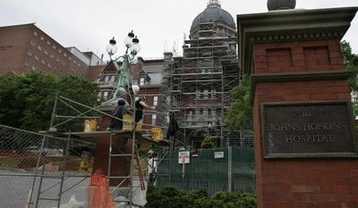 ** FILE ** In this May 19, 2005, file photo, construction workers work on part of the Johns Hopkins Hospital in Baltimore. (AP Photo/Chris Gardner, File)