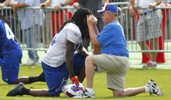 Buffalo Bills wide receiver Sammy Watkins (14) is tended to by trainer Bud Carpenter during their NFL football training camp in Pittsford, N.Y., Monday, July 21, 2014. Watkins returned to the field. (AP Photo/Bill Wippert)