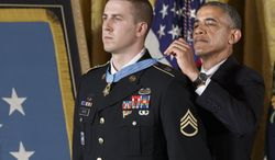 President Barack Obama bestows the Medal of Honor, the nation's highest decoration for battlefield valor, to Ryan M. Pitts, 28, of Nashua, NH, a former Army staff sergeant who fought off enemy fighters during one of the bloodiest battles of the Afghanistan war despite his own critical injuries, in the East Room of the White House in Washington, Monday, July 21, 2014. (AP Photo/J. Scott Applewhite)