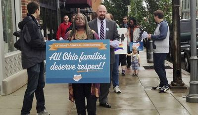 **FILE** Gay marriage supporters march to the office of Ohio Attorney General Mike DeWine in Columbus, Ohio, on May 15, 2014, to deliver petitions urging him to drop his appeal of a federal judge's order on same-sex marriage. The group, Why Marriage Matters Ohio, delivered over 6,000 signatures to DeWine's office, demanding he stop the appeal. (Associated Press)