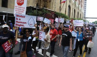 Protesters march over the controversial water shut-offs Friday, July 18, 2014, in Detroit, Mich.  (AP Photo/Detroit News, David Coates)
