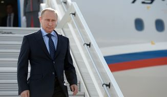 """Russian President Vladimir Putin steps down upon his arrival at the airport of Samara, Russia, Monday, July 21, 2014. Putin has lambasted those who use the downing of a passenger jet in eastern Ukraine for """"mercenary objectives,"""" the Kremlin said Monday. In a statement posted on the Kremlin website, Putin again lashed out at Ukraine for ongoing violence with pro-Russian rebels in the eastern part of the country. (AP Photo/RIA-Novosti, Alexei Nikolsky, Presidential Press Service)"""