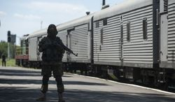 A pro-Russian armed fighter stands in guard on the platform as a refrigerated train loaded with bodies of the passengers departs the station in Torez, eastern Ukraine, 15 kilometers (9 miles) from the crash site of Malaysia Airlines Flight 17, Monday, July 21, 2014. Another 21 bodies have been found in the sprawling fields of east Ukraine where Malaysia Airlines Flight 17 was downed last week, killing all 298 people aboard. International indignation over the incident has grown as investigators still only have limited access to the crash site and it remains unclear when and where the victims' bodies will be transported. (AP Photo/Evgeniy Maloletka)