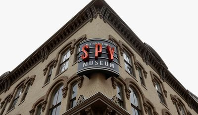 A sign for the International Spy Museum is lit up around the corner from the Adams Building. The museum is one of the hottest attractions in the nation's capital. (ASSOCIATED PRESS)