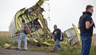 Malaysian air crash investigators walk by wreckage at the crash site of Malaysia Airlines Flight 17 near the village of Hrabove, eastern Ukraine, Tuesday, July 22, 2014. A team of Malaysian investigators visited the site along with members of the OSCE mission in Ukraine for the first time since the air crash last week.(AP Photo/Vadim Ghirda)
