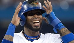 Toronto Blue Jays shortstop Jose Reyes smiles after hitting a single against the Boston Red Sox during the seventh inning of a baseball game, Tuesday, July 22, 2014 in Toronto. (AP Photo/The Canadian Press, Nathan Denette)