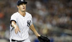 New York Yankees starting pitcher Shane Greene overthrows to first, committing his third error trying to put out Texas Rangers Rougned Odor in the fourth inning of a baseball game at Yankee Stadium in New York, Monday, July 21, 2014.  (AP Photo/Kathy Willens)