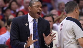 Los Angeles Clippers head coach Doc Rivers, left, talks to referee Monty McCutchen, center, in the second half of Game 6 of the Western Conference semifinal NBA basketball playoff series against the Oklahoma City Thunder, Thursday, May 15, 2014, in Los Angeles. The Thunder won104-98, taking the series 4-2.  (AP Photo/Mark J. Terrill)