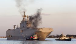 FILE - In this March 5, 2014 file photo, French-built warship BPC Vladivostock, designed to strengthen Russia's ability to deploy troops, tanks and helicopter gunships, leaves the Saint Nazaire's harbor, western France, for its test run on the open sea off coast of France. French President Francois Hollande is defending plans to deliver a 1.1 billion-euro French-made warship to Russia, despite increasing pressure for tougher European sanctions against Moscow over the fighting in Ukraine. European Union foreign ministers are meeting Tuesday July 22, 2014 in Brussels, with some calling for an arms embargo or other new punishment against Russia. (AP Photo/David Vincent, File)