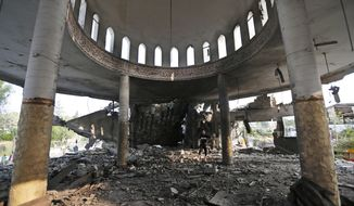 A Palestinian walks inside the Al Aqsa Martyrs mosque destroyed by an overnight Israeli strike, in Gaza City, Tuesday, July 22, 2014. (AP Photo/Lefteris Pitarakis) ** FILE **