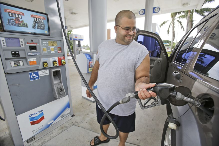 In this Wednesday, June 4, 2014, photo, Baltazar Rosado, of Hollywood, Fla., pumps gasoline into his car at a Chevron gasoline station in Pembroke Pines, Fla. The Labor Department reports on U.S. consumer prices in June on Tuesday, July 22, 2014. (AP Photo/Wilfredo Lee)