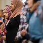 70 citizenship candidates stand for the National Anthem before being sworn in as U.S. Citizens at a Naturalization Ceremony at the Department of Justice, Washington, D.C., Tuesday, July 22, 2014. (Andrew Harnik/The Washington Times)