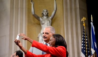 Lusamba Ejiba of Leesburg, Va., originally from the Democratic Republic of Congo, takes a selfie photograph with Attorney General Eric Holder after she is sworn in as a U.S. Citizen at a Naturalization Ceremony at the Department of Justice, Washington, D.C., Tuesday, July 22, 2014. (Andrew Harnik/The Washington Times)