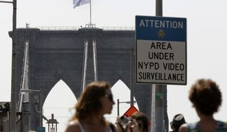 """A white flag flies atop the west tower of New York's Brooklyn Bridge, Tuesday, July 22, 2014. Someone replaced two American flags on the bridge with mysterious white flags. The white flags, international symbols of surrender, fluttered from poles on the stone supports that hold cables above the bridge connecting Brooklyn and Manhattan. An entity called Bike Lobby tweeted Tuesday that it hoisted the flags to signal """"surrender of the Brooklyn Bridge bicycle path to pedestrians.""""  (AP Photo/Richard Drew)"""