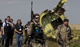 A pro-Russian rebel holds a gun passing by plane wreckage as members of the OSCE mission to Ukraine arrive for a media briefing at the crash site of Malaysia Airlines Flight 17, near the village of Hrabove, eastern Ukraine, Tuesday, July 22, 2014. (AP Photo/Vadim Ghirda) ** FIL E**