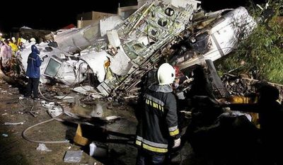 Rescue workers survey the wreckage of TransAsia Airways flight GE222, which crashed while attempting to land in stormy weather on the Taiwanese island of Penghu. Experts say the airline industry will stay healthy despite several recent tragedies. (Associated Press)