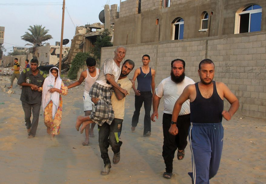 A Palestinian man carries his father as he and others run to take cover during an Israeli air strike in Rafah on Wednesday. (Associated Press photographs)