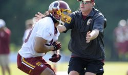 FILE - In this June 17, 2014 file photo, Washington Redskins head coach Jay Gruden takes part in a drill with running back Roy Helu, Jr., left, during an NFL football minicamp in Ashburn, Va. After years of waiting for his turn, and after months of meticulous planning, Jay Gruden begins his first NFL training camp as a head coach as the Redskins report to their facilities in Richmond, Va. (AP Photo/Nick Wass, File)