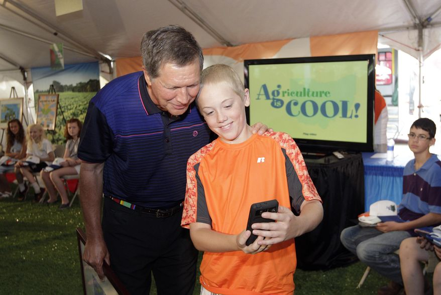 Brandon Barr, 11, right, of Xenia, takes a selfie with Ohio Gov. John Kasich after winning first place in the art contest at the Agriculture is Cool tent at the Ohio State Fair Wednesday, July 23, 2014, in Columbus, Ohio. Gov. Kasich joined general manager Virgil Strickler in opening ceremonies Wednesday. (AP Photo/Jay LaPrete)