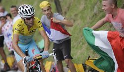 A fan waves the Italian flag as stage winner and overall leader Vincenzo Nibali of Italy climbs towards Hautacam during the eighteenth stage of the Tour de France cycling race over 145.5 kilometers (90.4 miles) with start in Pau and finish in Hautacam, Pyrenees region, France, Thursday, July 24, 2014. (AP Photo/Laurent Cipriani)