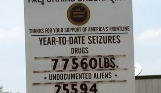 In this photo taken on Thursday, July 17, 2014,  a sign at the Falfurrias Station's U.S. Border Patrol checkpoint about 70 miles north of McAllen, Texas, shows the tally of drugs and illegal immigrants taken in this year. (AP Photo/The Abilene Reporter-News, Ronald W. Erdrich)