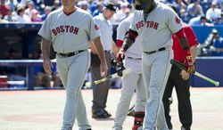 Boston Red Sox manager John Farrell, left, walks back to the dugout with designated hitter David Ortiz, right, after Ortiz injured himself in the ninth inning of a baseball game against the Toronto Blue Jays in Toronto on Thursday, July 24, 2014. (AP Photo/The Canadian Press, Nathan Denette)