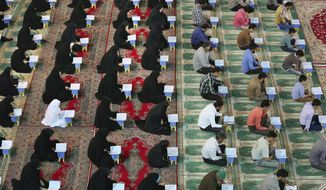Iranian men, right, and women recite verses of the Quran, Islam's holy book, at the shrine of Saint Mohammad Helal Ibn Ali in the city of Aran and Bidgol, some 140 miles south of the capital Tehran, Iran. Three Americans were detained in Tehran, including a reporter for The Washington Post.  (AP Photo/Vahid Salemi)
