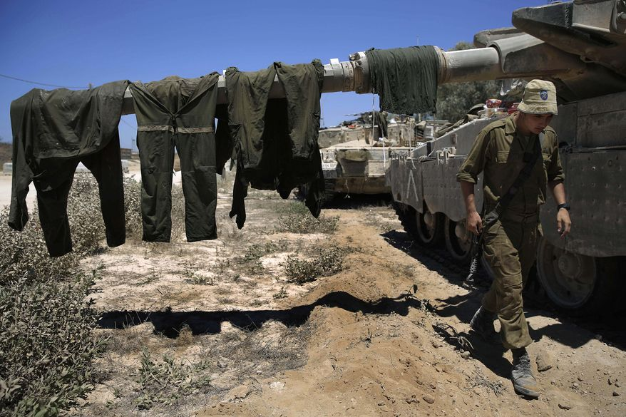An Israeli soldier walks under a barrel of a tank where soldiers' overalls hang for drying in a gathering area near the Israel and Gaza border, Thursday, July 24, 2014. Israeli tanks and warplanes bombarded the Gaza Strip on Thursday, as Hamas militants stuck to their demand for the lifting of an Israeli and Egyptian blockade in the face of U.S. efforts to reach a cease-fire. (AP Photo/Tsafrir Abayov)