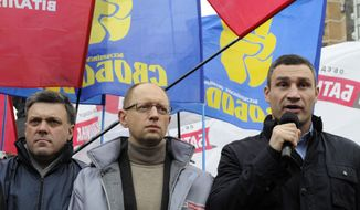 ** FILE ** In this Monday, Nov. 5, 2012 file photo, Oleh Tyahnybok, leader of the nationalist Svoboda party, left, Ukrainian opposition leader Arseniy Yatsenyuk, center, and Chairman of the Ukrainian opposition party UDAR (Punch) and WBC Heavyweight Champion boxer Vitali Klitschko, right, take part in a rally outside the Central Elections Commission building in Kiev, Ukraine. Ukrainian Prime Minister Arseniy Yatsenyuk announced his resignation on Thursday, July 24, 2014, following turmoil in government. (AP Photo/Sergei Chuzavkov, File)