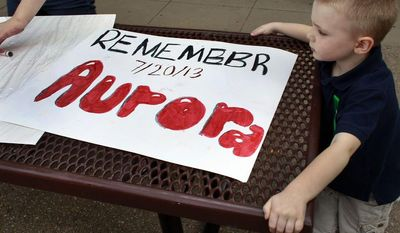 """** FILE ** In this  July 19, 2013, file photo, 4-year-old Jake Richards watches as his sister Stephanie makes signs reading """"Remember Aurora,"""" during a remembrance event at which the names of people killed by gun violence in America over the previous year were read aloud, at Cherry Creek State Park in Aurora, Colo. (AP Photo/Brennan Linsley, file)"""