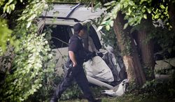 A police officer walks past the wreckage of a carjacked vehicle that police say hit a group of people on a corner in Philadelphia on Friday, July 25, 2014, killing two children and critically injuring three other people. One of the children was pronounced dead at the scene and another at a hospital, Homicide Capt. James Clark said.  (AP Photo/Philadelphia Daily News, Alejandro A. Alvarez) MANDATORY CREDIT; THE EVENING BULLETIN OUT, TV OUT; MAGS OUT; NO SALES