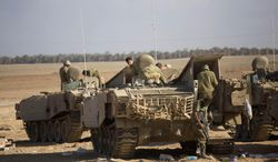 Israeli soldiers work on their armored personnel carriers near the Israel and Gaza border Friday, July 25, 2014. Early Friday, Israeli warplanes struck tens of houses throughout the Gaza Strip as international efforts continue to broker a cease fire in the 18 day-old war. (AP Photo/Dusan Vranic)