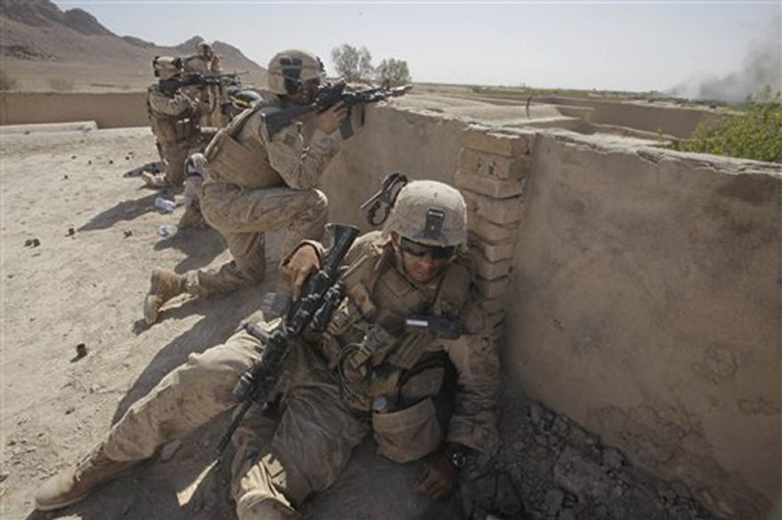 ** FILE ** U.S. Marines take cover in Dahaneh, a long-standing Taliban stronghold in southern Helmand Province. (Associated Press)