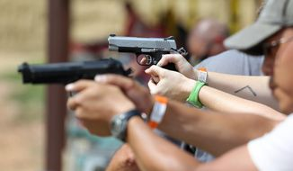 ** FILE ** In this July 20, 2014, photo, shooters practice with pistols at the gun range at Dragonman's, a gun dealer east of Colorado Springs, Colo. (AP Photo/Brennan Linsley)