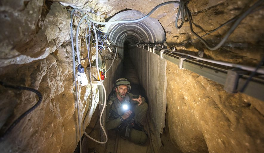 "An Israeli army officer gives journalists a tour, Friday, July 25, 2014, of a tunnel allegedly used by Palestinian militants for cross-border attacks, at the Israel-Gaza Border. A network of tunnels Palestinian militants have dug from Gaza to Israel, dubbed ""lower Gaza"" by the Israeli military, is taking center stage in the latest war between Hamas and Israel. (AP Photo/Jack Guez, Pool)"