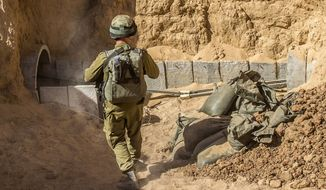 "An Israeli army officer walks near the entrance of a tunnel, Friday, July 25, 2014, that is allegedly used by Palestinian militants for cross-border attacks, at the Israel-Gaza Border. A network of tunnels Palestinian militants have dug from Gaza to Israel, dubbed ""lower Gaza"" by the Israeli military, is taking center stage in the latest war between Hamas and Israel. (AP Photo/Jack Guez, Pool)"