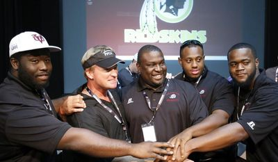 ESPN broadcaster and former NFL head football coach Jon Gruden, second from left, poses for a picture with members of the coaching staff with Virginia Union University after a Redskins Charitable Foundation clinic for coaches, Friday, July 25, 2014 in Richmond, Va. (AP Photo)