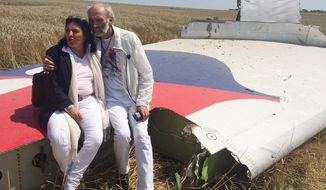 "Jerzy Dyczynski and Angela Rudhart-Dyczynski whose daughter, 25-year-old Fatima, was a passenger on Malaysia Airlines flight MH17, sit on part of the wreckage of the crashed aircraft in Hrabove, Ukraine, Saturday, July 26, 2014. The couple who live in Perth, Australia, crossed territory held by pro-Russian rebels to reach the wreckage-strewn farm fields outside the village of Hrabove. They last spoke to Fatima shortly before she boarded the flight for Kuala Lumpur in Amsterdam on July 17. Rudhart-Dyczynski said, ""We have promised our daughter we will come here.""  (AP Photo/Nicholas Garriga)"
