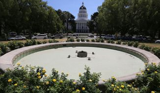 In this photo taken Monday, July 21, 2014, is the unused water fountain located across the street from the state Capitol in Sacramento, Calif.  The fountain was drained earlier in the year for repairs, but due to the one of the worst droughts in California history, the repairs and refilling the fountain have been delayed.   (AP Photo/Rich Pedroncelli)