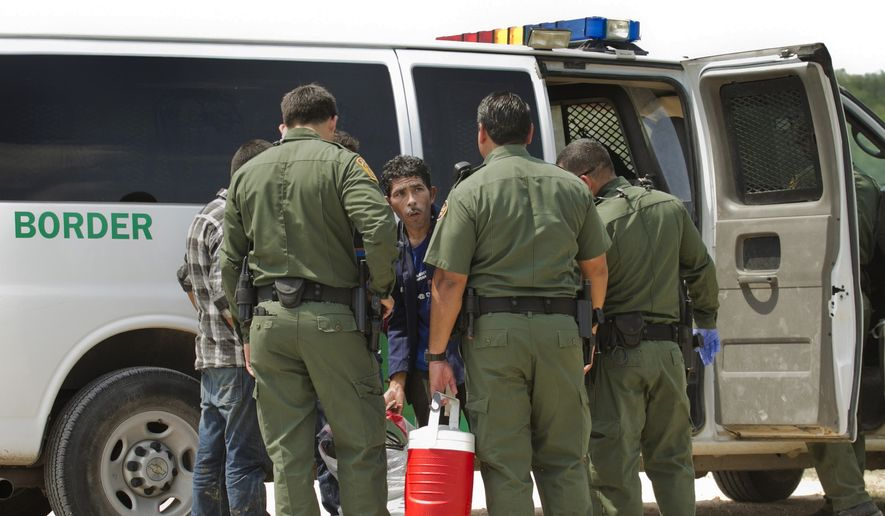 In this Thursday, July 24, 2014, photo, U.S. Border Patrol agents apprehend men who crossed the Rio Grande River from Reynosa, Tamaulipas, Mexico, in Anzalduas Park in McAllen, Texas. (AP Photo/Austin American-Statesman, Jay Janner)