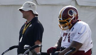 Washington Redskins tackle Trent Williams pauses on an exercise bicycle during practice at the team's NFL football training facility, Saturday, July 26, 2014 in Richmond, Va. (AP Photo)