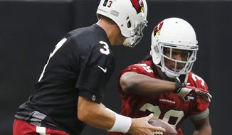 Arizona Cardinals' Carson Palmer (3) hands the ball off to Andre Ellington, right, during the first day of NFL football training camp on Saturday, July 26, 2014, in Glendale, Ariz. (AP Photo/Ross D. Franklin)
