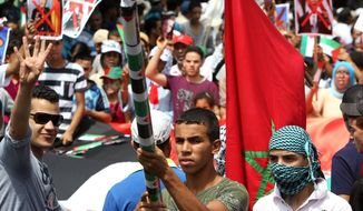 A Moroccan flag is displayed as thousands of pro-Palestinian demonstrators holds banners and shout slogans during a protest against the Israeli offensive on the Gaza Strip, in the streets of Casablanca, Morocco, Sunday, July 27, 2014. Israel and Hamas launched new attacks Sunday in the raging Gaza war, despite each side offering different truces to temporarily halt nearly three weeks of fighting ahead of a major Muslim holiday. (AP Photo/Abdeljalil Bounhar)