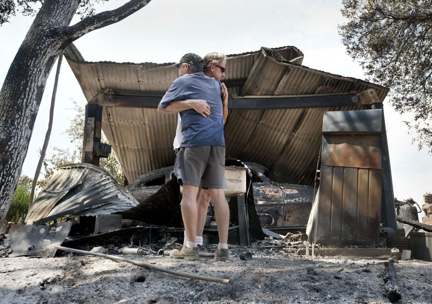 Bill Cleek, left, embraces his good friend, Terry Cromwell outside a structure which housed one of many antique cars destroyed by a fire at Rancho Cicada Retreat on Sunday, July 27, 2014, in Plymouth, Calif. Firefighters in Northern California on Sunday battled a wildfire that has destroyed 10 homes and forced hundreds of evacuations in the Sierra Nevada foothills, while a fire near Yosemite National Park destroyed one home and grew significantly overnight. (AP Photo/The Sacramento Bee, Randy Pench)