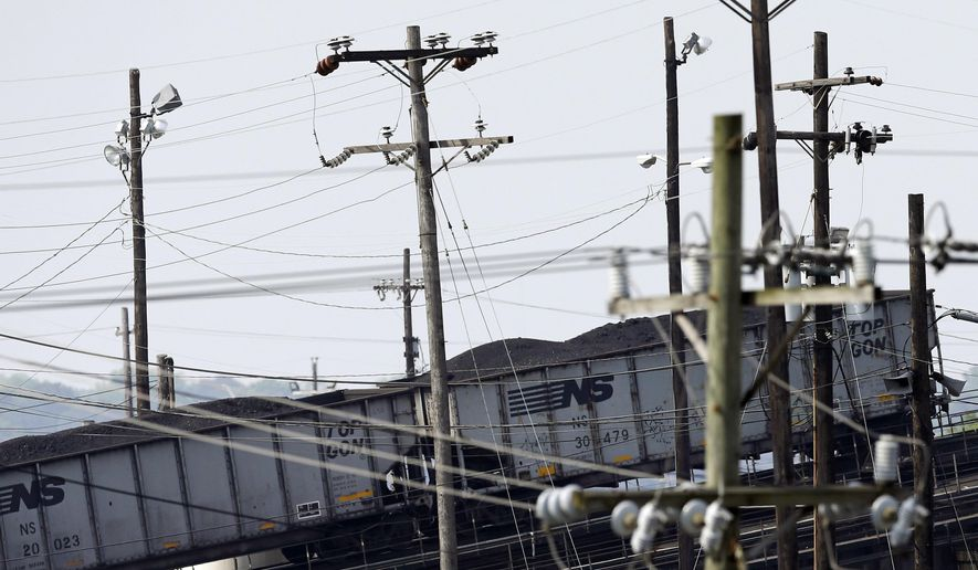 In this May 22, 2014, photo, train cars containing coal are seen past power lines as they are pushed up an incline before being unloaded at Norfolk Southern's Lamberts Point coal terminal in Norfolk, Va. As the Obama administration weans the U.S. off dirty fuels blamed for global warming, energy companies have been sending more of America's unwanted energy leftovers to other parts of the world where they could create even more pollution. (AP Photo/Patrick Semansky)
