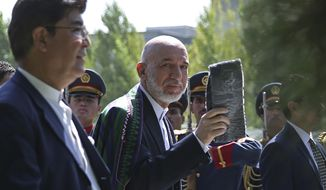 Afghanistan's President Hamid Karzai, center, leaves after Eid al-Fitr prayer at the presidential palace in Kabul, Afghanistan, Monday, July 28, 2014. Eid al-Fitr prayer marks the end of the holy fasting month of Ramadan in Afghanistan. (AP Photo/Massoud Hossaini)
