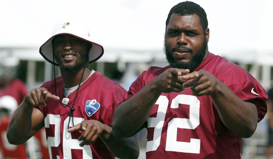Washington Redskins cornerback Bashaud Breeland, left, and defensive lineman Chris Baker gesture toward members of the media as they walk on the field during practice at the team's NFL football training facility, Sunday, July 27, 2014, in Richmond, Va. (AP Photo/Alex Brandon)
