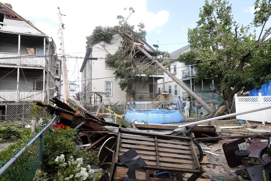 People observe the damage in the back of several houses in Revere, Mass. Monday, July 28, 2014, after a tornado touched down. Revere Deputy Fire Chief Mike Viviano says the fire department in that coastal city has received dozens of calls reporting partial building and roof collapses, and downed trees and power lines. Viviano says there are no immediate reports of deaths or serious injuries. (AP Photo/Elise Amendola)